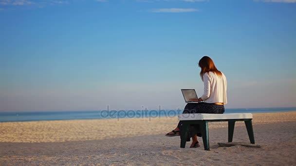 kaukázusi lány ír szöveget a laptop ül a padon a strand, a tengerpart mentén buborékok