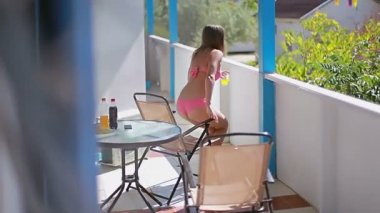 Young girl sitting in a chair on the balcony with the tablet.
