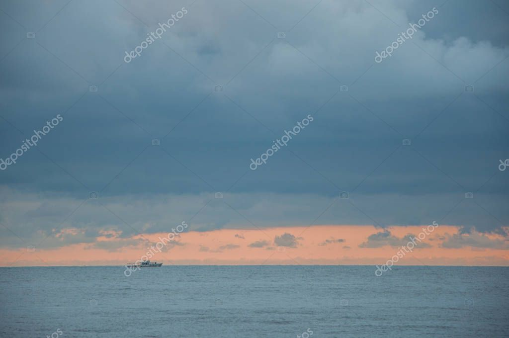 seascape in blue with a ship on the horizon