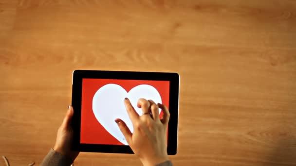 Žena kreslení srdce srdce pohled na tabletu