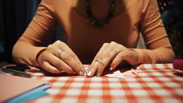 Female making origami heart from pink paper for valentines day