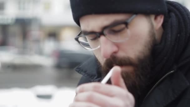 Hipster man smoking cigarette on the street