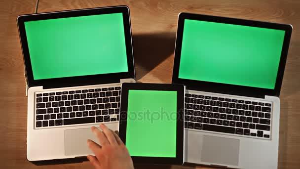 Pohled shora člověka pomocí digitálního tabletu a dva notebooky