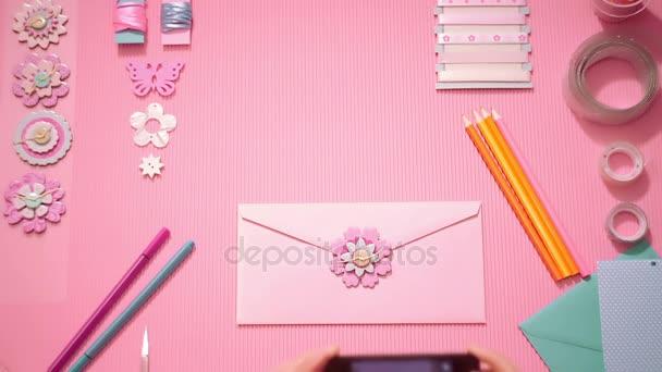 Felülnézet lány így egy fénykép smartphone ünnepi rózsaszín boríték