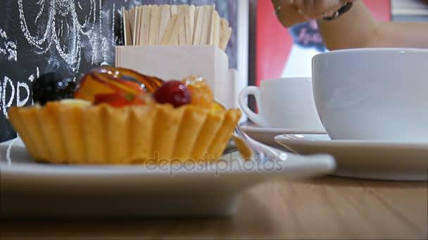 Detail nalil a za stálého míchání cukr v kávě s ovocný koláč na popředí