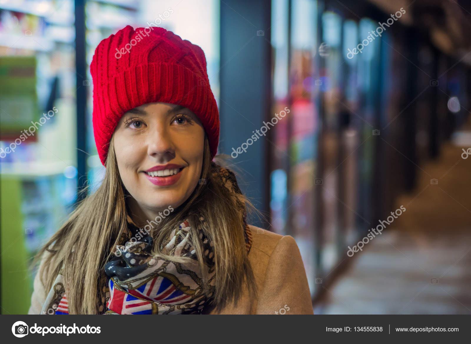 Retrato natural de uma mulher bonita e sorridente de chapéu vermelho gorro  de lã tricotado em um close-up tiro na cabeça. Beleza comprar compras  descontos ... 16d0b95e602