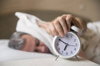 sleeping man disturbed by alarm clock early morning.  Sleepy young man covering ears with pillow as he looks at alarm clock in be