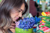 young pretty woman with spring flowers bouquet. Woman smelling bouquet of hyacinth