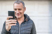 happy mature man using cell phone on city street