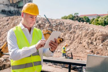 portrait of smiling civil engineer in yellow hardhat using digital tablet at construction site