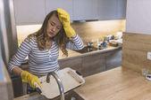 Fotografie Hand-Reinigung. Junge Hausfrau Frau beim Abwasch in der Küche. Junge Brünette Frau Abwasch manuell, per hand, gelbe Reinigung Gummihandschuhe tragen. Müde von der Reinigung