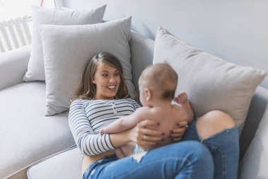 We play, learn and grow together.  Young mother playing with her baby son at home. mother playing with baby. Portrait of a happy mother hugging cute baby on bed. Beautiful young mom is playing with her cute baby and smiling