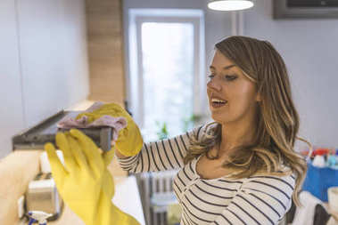 Young woman cleaning cooker hood at home kitchen. Close up of female hands in rubber protective yellow gloves cleaning the kitchen metal extractor hood with rag. Home, housekeeping concept.