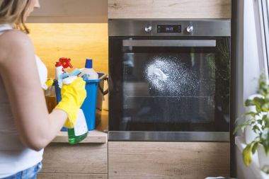 Close up of female hand with yellow protective gloves spraying detergent from bottle on the oven door.  young smiling woman in protective glove with rag cleaning oven. Girl polishing kitchen. People, housework, housekeeping, cleaning concept