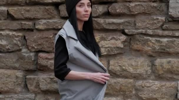 Stylish Fashion Girl, With Long Black Hair, Walking in the Street, on Background Brick Wall, in Grey Cloak and Black Hat