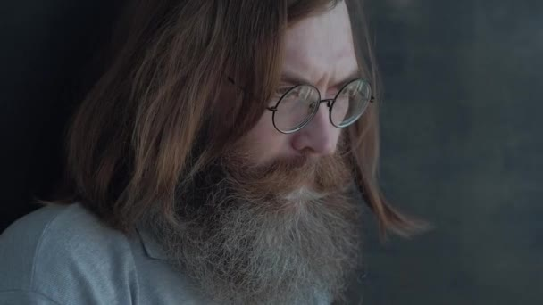 Pensive Man With Glasses Standing at the Window Thinking About Something, With a Gray Beard and Brown Lush Long Hair