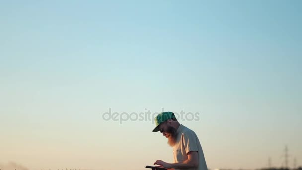 Mature Farmer With Big Beard Stay in Wheat Field and Using a Digital Tablet For Business