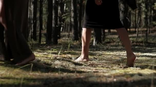 girls in dresses walking on the forest moss