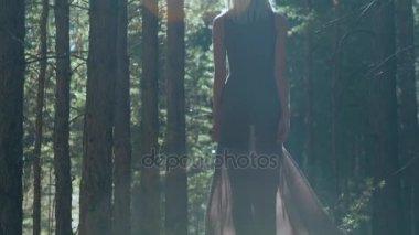 slender blonde walks in the woods