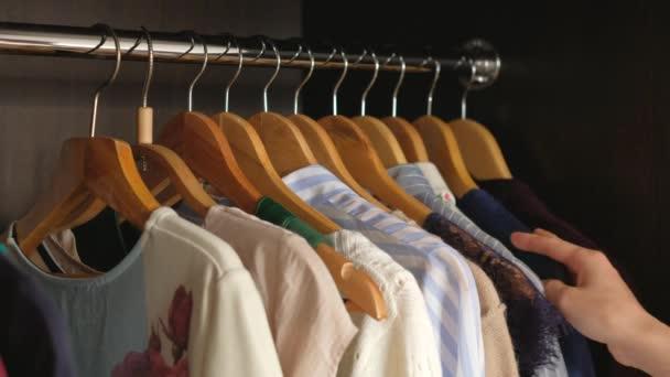Žena si vybírá oblečení do skříně