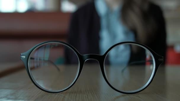 Nő vesz szemüveg a tábla, ruhák, magad