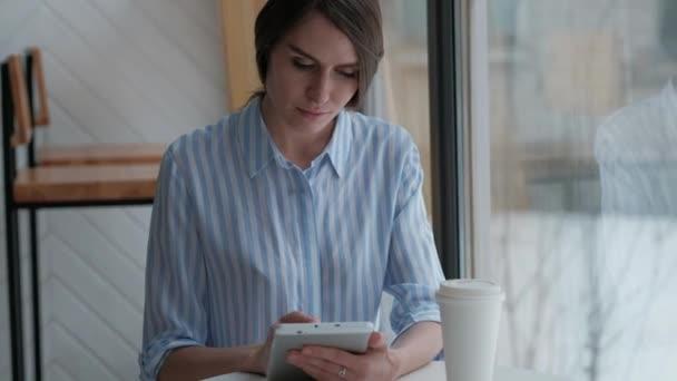 Roztomilé ženské sedí v kavárně a použití digitálních tablet