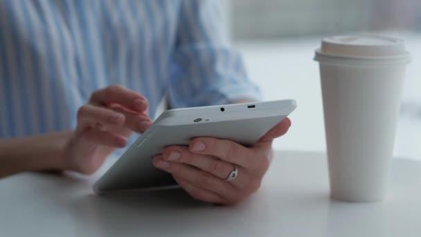 Ženské sedí v kavárně a použití digitálních tablet