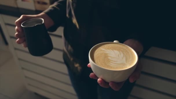 Close up of barista holding aromatic cappuccino. Coffee ready for sale.