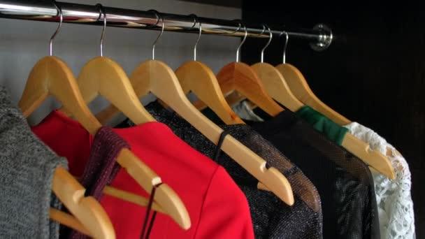 Žena ruka výběru šaty v šatníku pro večerní večeři nebo party.