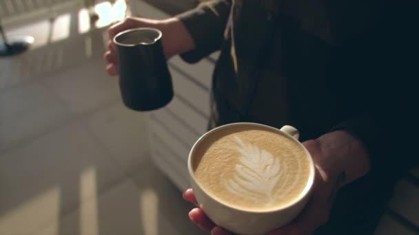 Közel a baristához, aki aromás cappuccinót tart. Eladásra kész kávé.