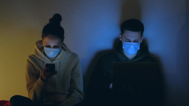 Young couple in medical masks using smartphone and laptop at night.