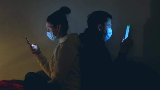 Coronavirus and quarantine concept. Bored young couple in medical masks using smartphone and laptop at night.