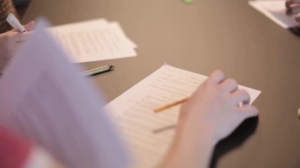 Shot of a persons hands while going over some papers and with somebody besides who is taking notes.