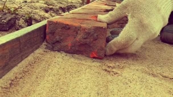 Dlažba. Stavitelovy ruce v bílých rukavicích s kladivem kladoucím staré červené cihly na pískový základ. Building