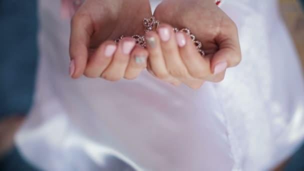 Dívka ukazuje v rukou šperky náušnice