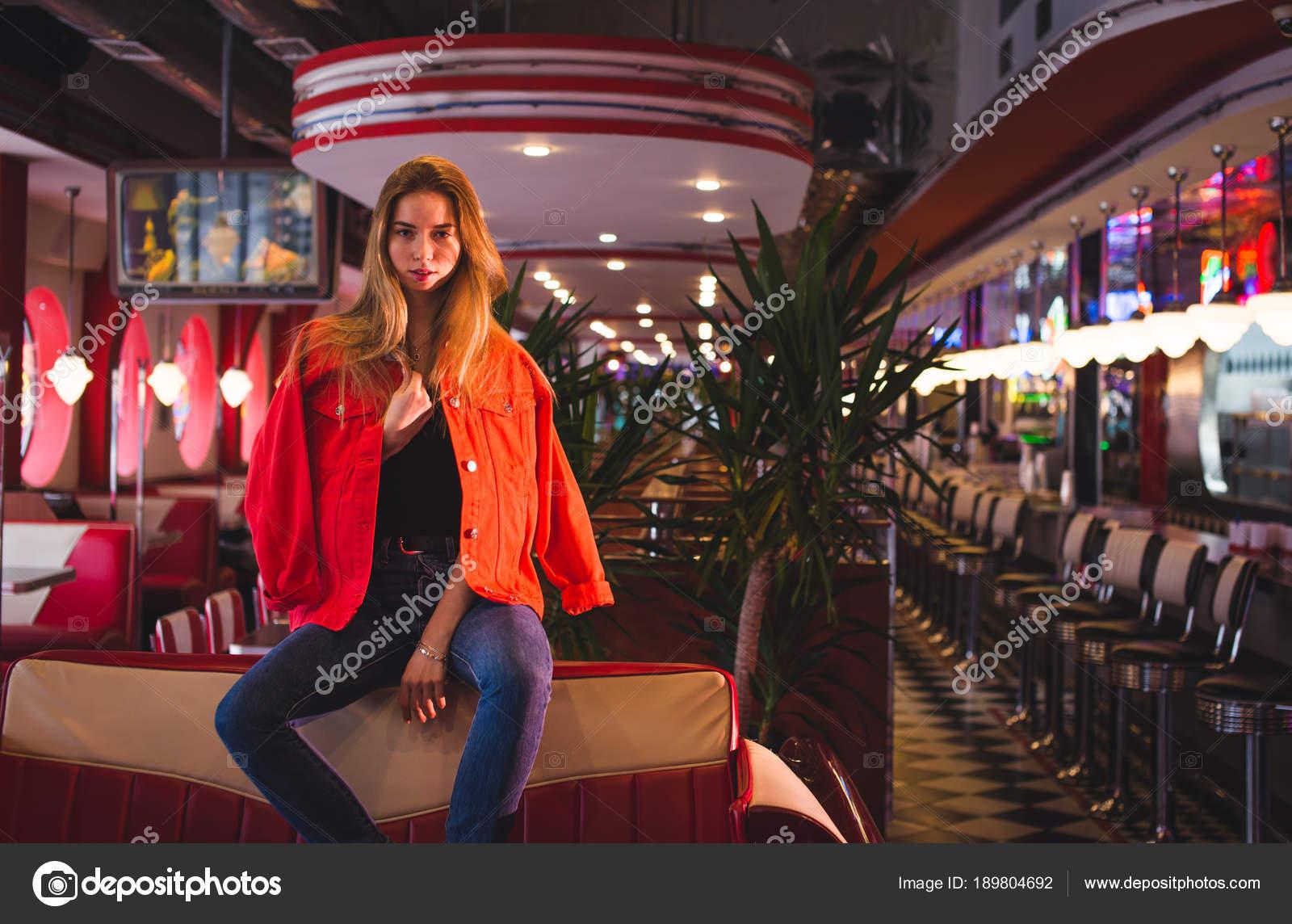 6820e95d509e Junge stilvolle schöne Frau sitzt in Stadt Café im roten Mantel ...