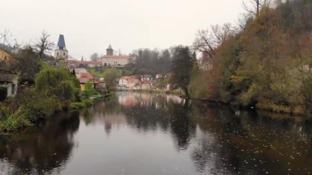 Let dronem přes řeku v malém historickém českém městečku na podzim. Pohled na kostel, hrad na kopci a řeku. Rozmberk nad Vltavou, Jižní Čechy