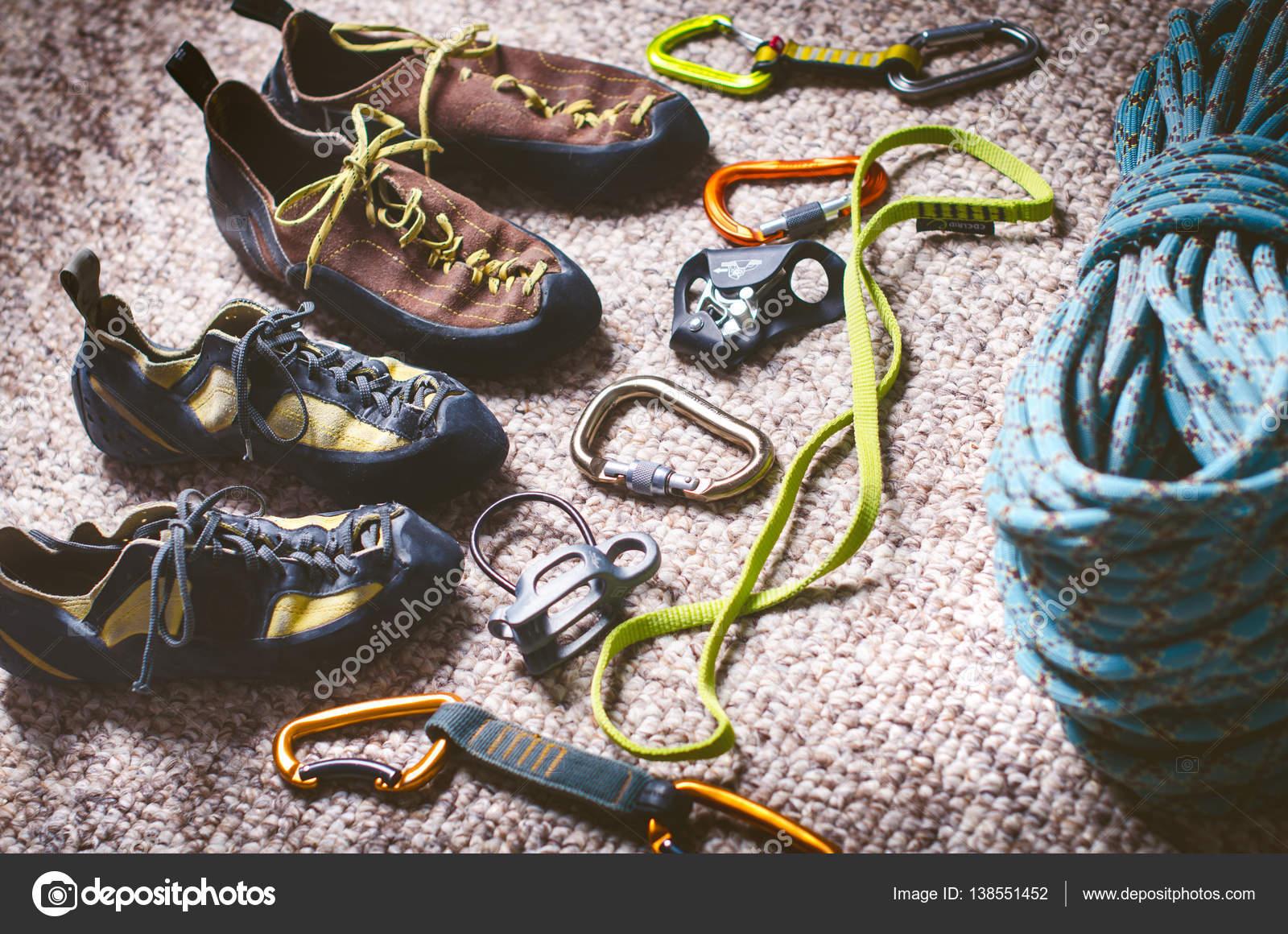 Klettern und Bergsteigerausrüstung auf einem Teppich. Schuhe ...