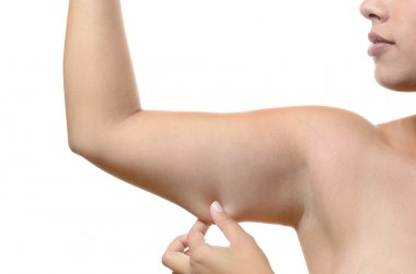 Young woman pinching the skin on her upper arm