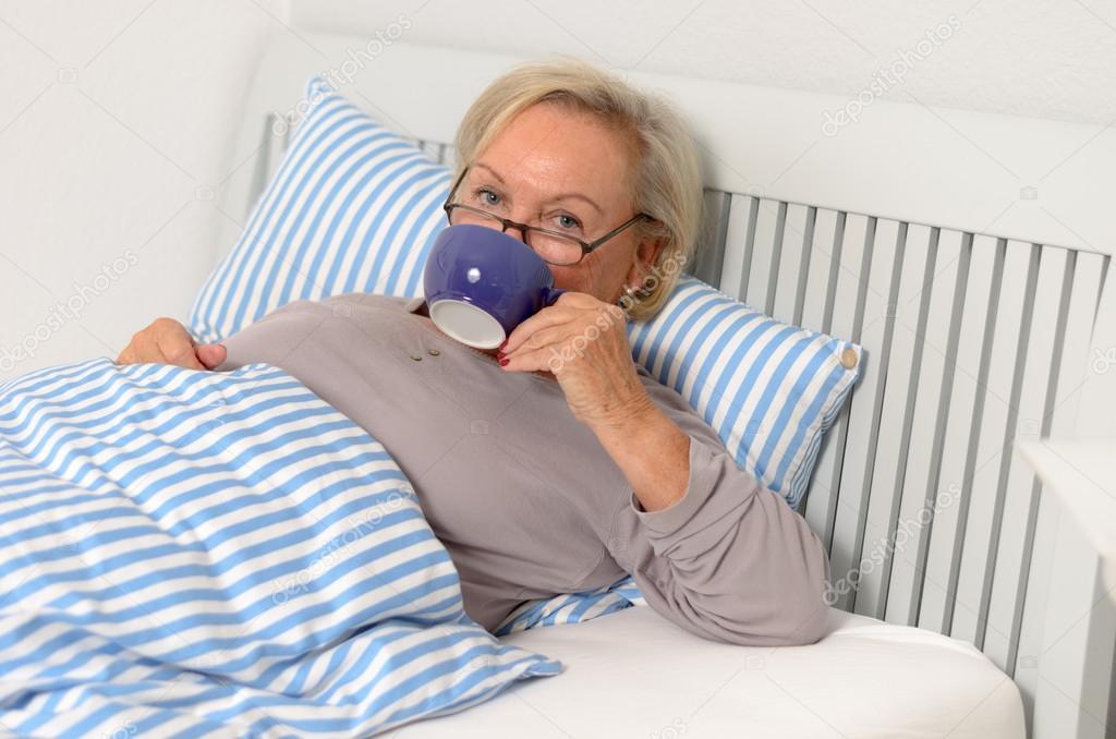 Volwassen blonde vrouw op haar bed holding haar cup u stockfoto
