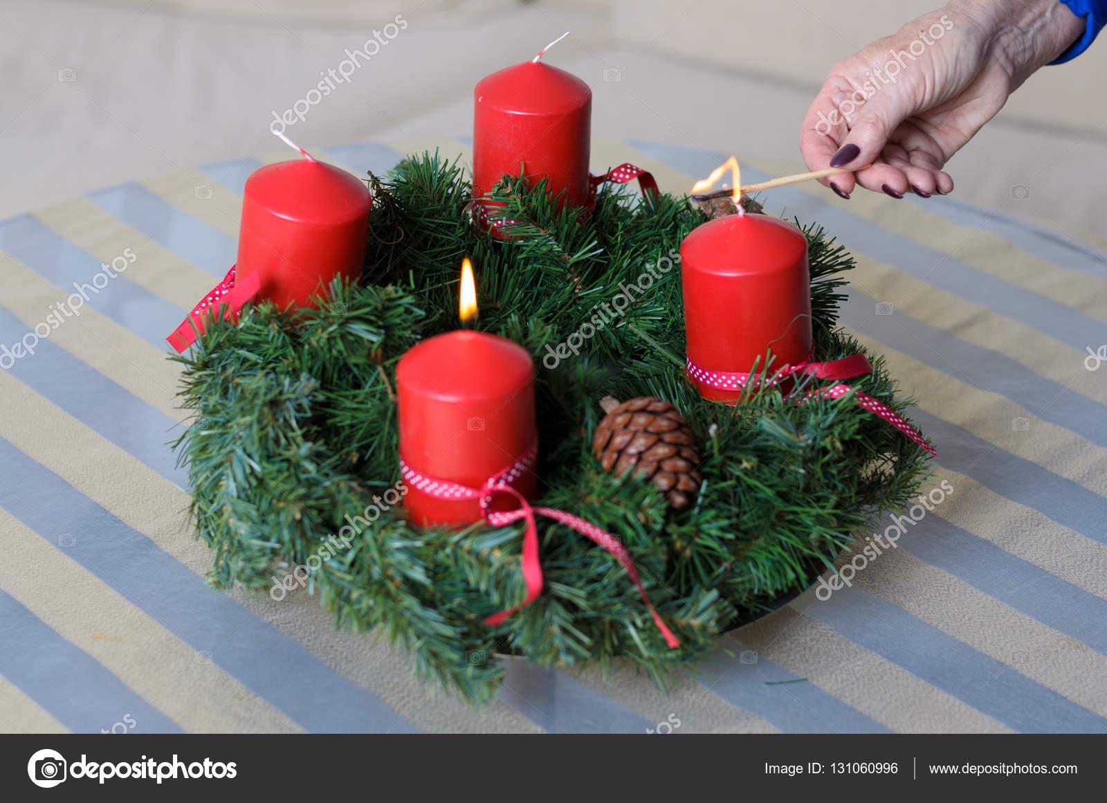 vrouw verlichting kaarsen op een kerst krans stockfoto