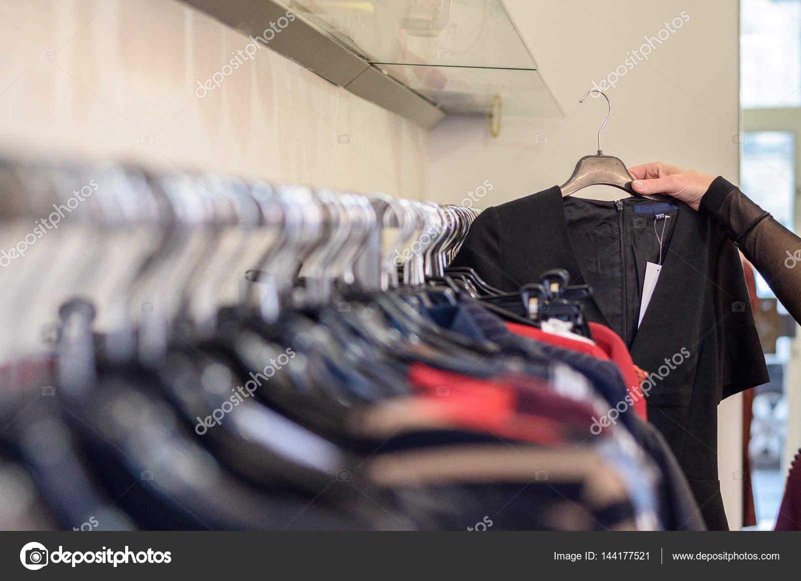 Kleding Zoeken.Vrouwelijke Shopper Zoeken Door Middel Van Kleding Stockfoto