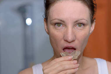 Woman placing a bite plate in her mouth