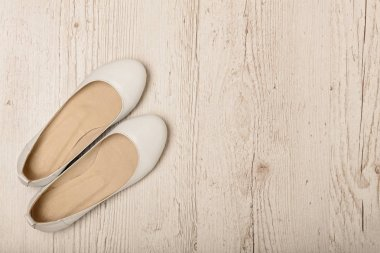 Women shoes (ballet flats) white color on a light wooden backgro