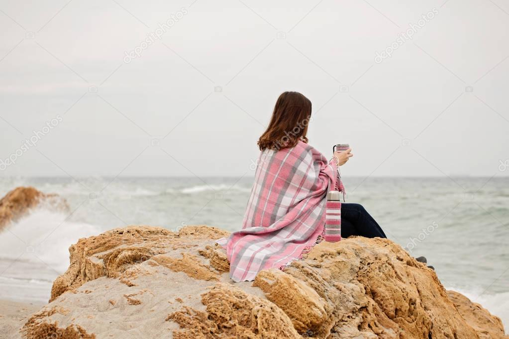 Young woman is covered with a rug sits on the seashore and drink