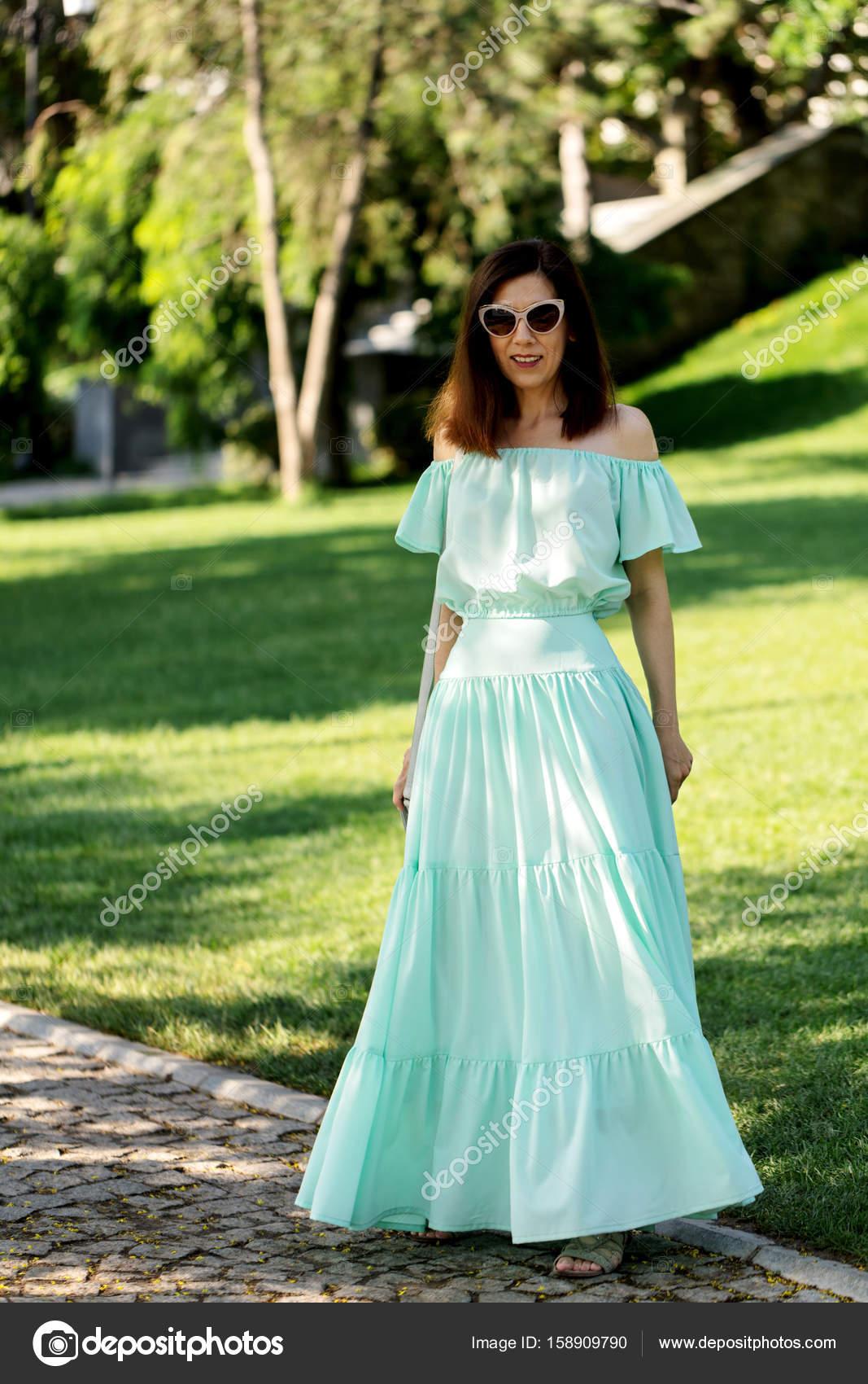 2f98267c7621 Νεαρή όμορφη γυναίκα σε ένα ελαφρύ παστέλ πράσινο μακρύ φόρεμα είναι με τα  πόδια — Φωτογραφία