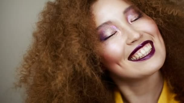 Beautiful Asian girl with bright makeup and curly hair smiling happily