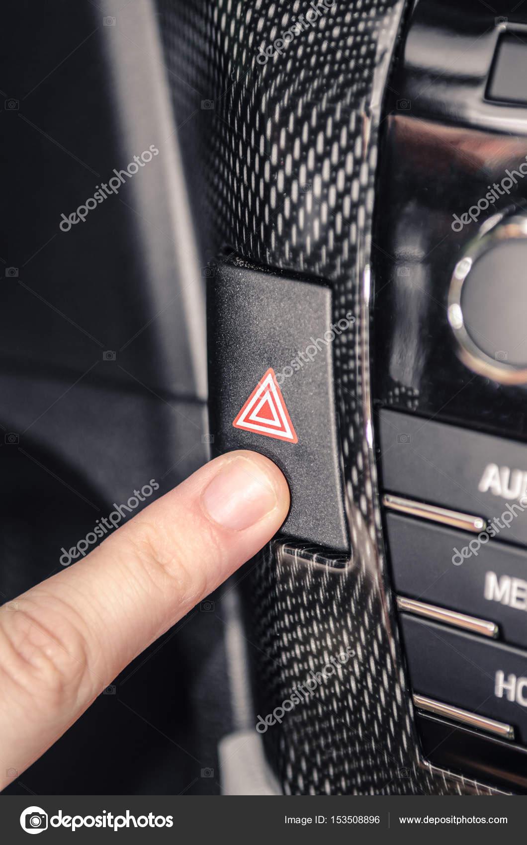 finger pressing the car warning flashing button. — stock photo