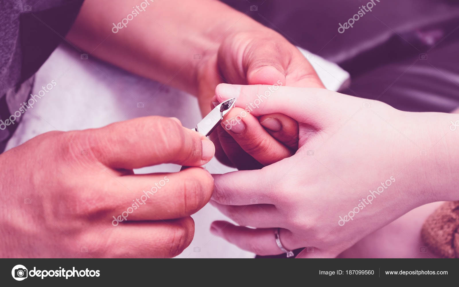 Manicurist using pliers to remove dead skin from around the clie ...