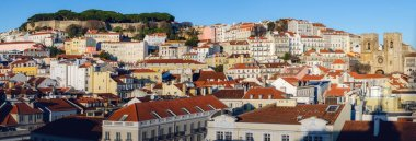 Sunset panorama of Alfama neighborhood in Lisbon, Portugal, with the famous castle of Sao Jorge on the hilltop and the cathedral of Santa Maria Maior bettween the tooftops